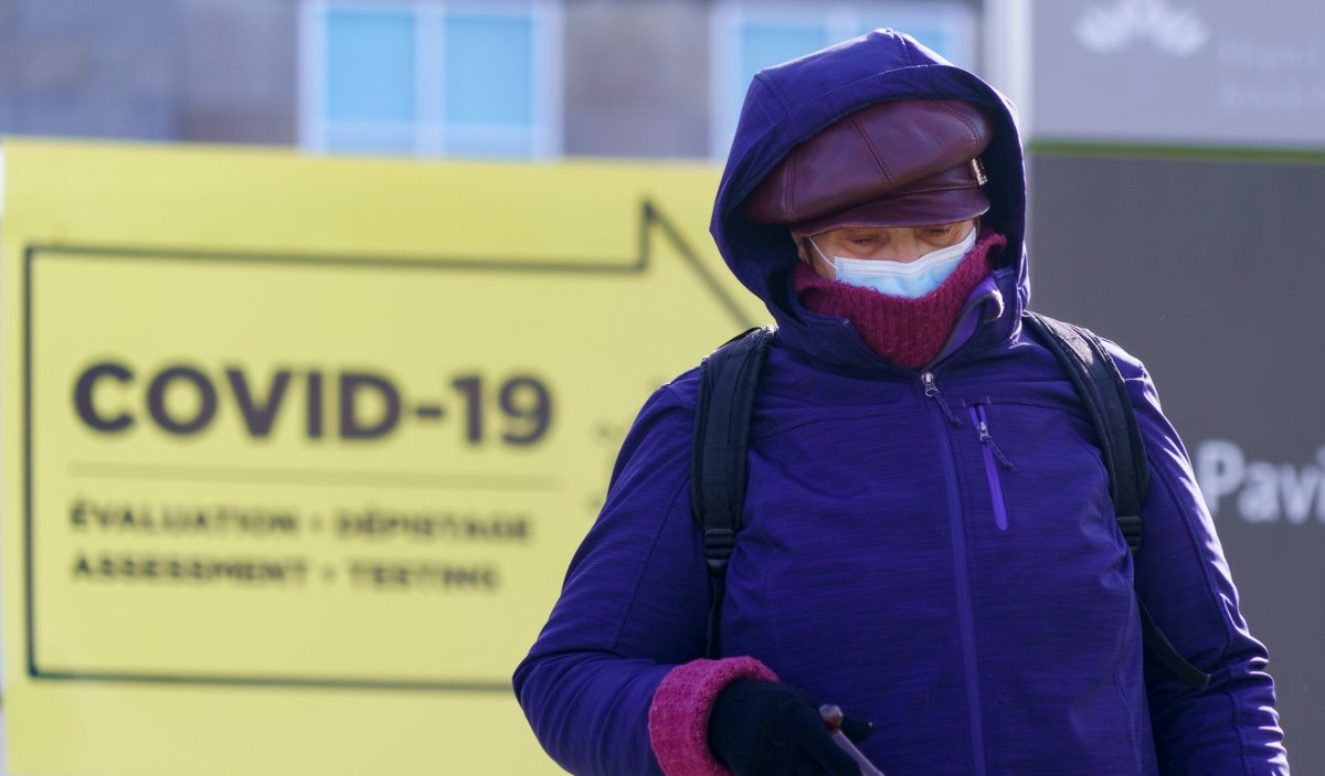 A woman all bundled up walks past a COVID-19 test clinic during a brisk fall morning in Montreal, on Friday, Oct. 30, 2020.