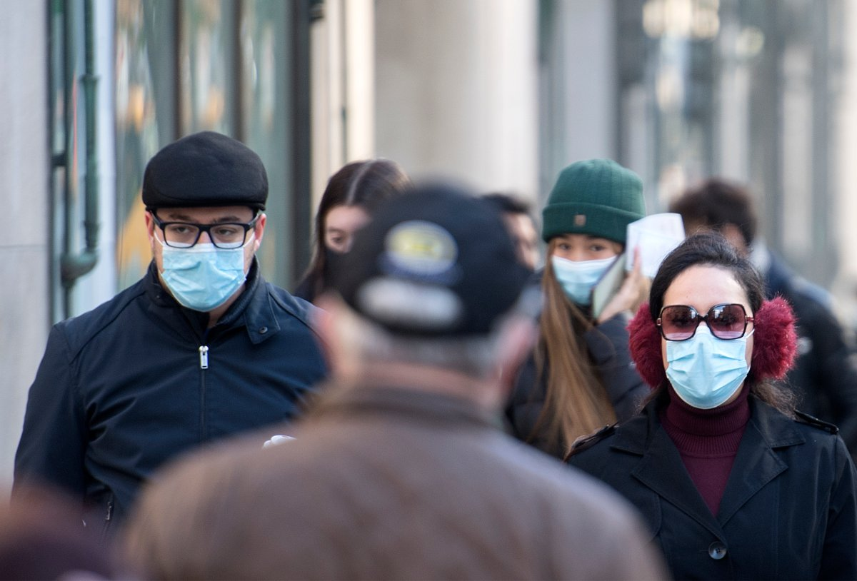 People wear face masks as they cross a street in Montreal, Saturday, October 31, 2020, as the COVID-19 pandemic continues in Canada and around the world.