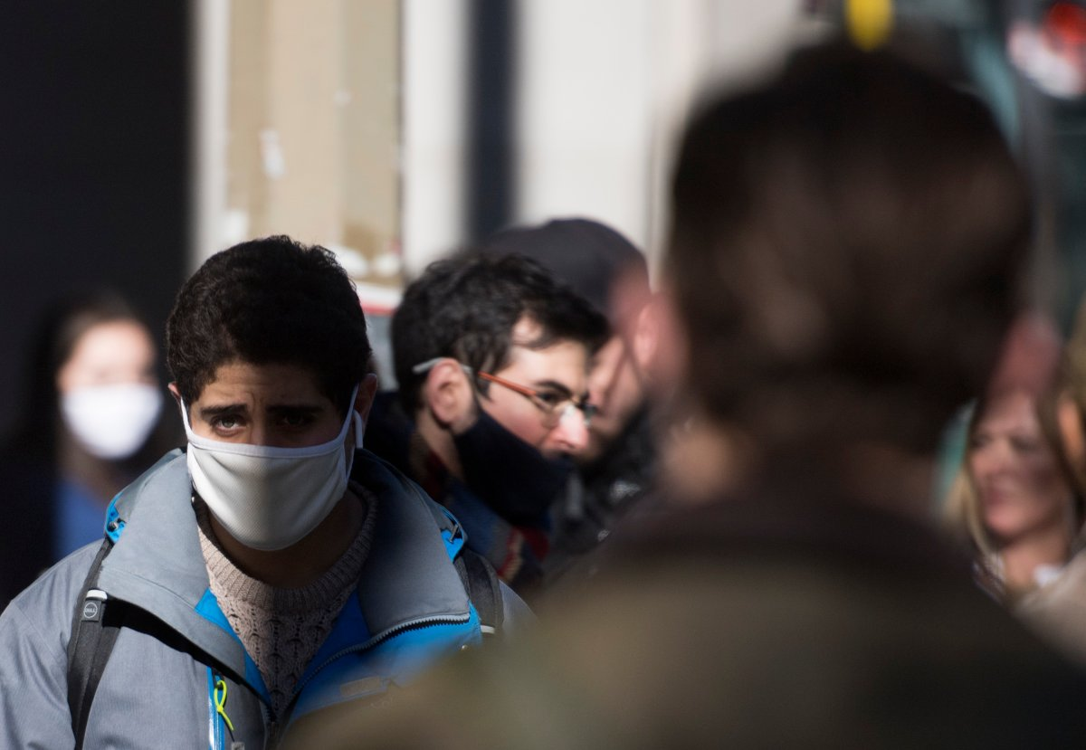 People wear face masks as they walk along a street in Montreal, Saturday, Oct. 31, 2020, as the COVID-19 pandemic continues in Canada and around the world.