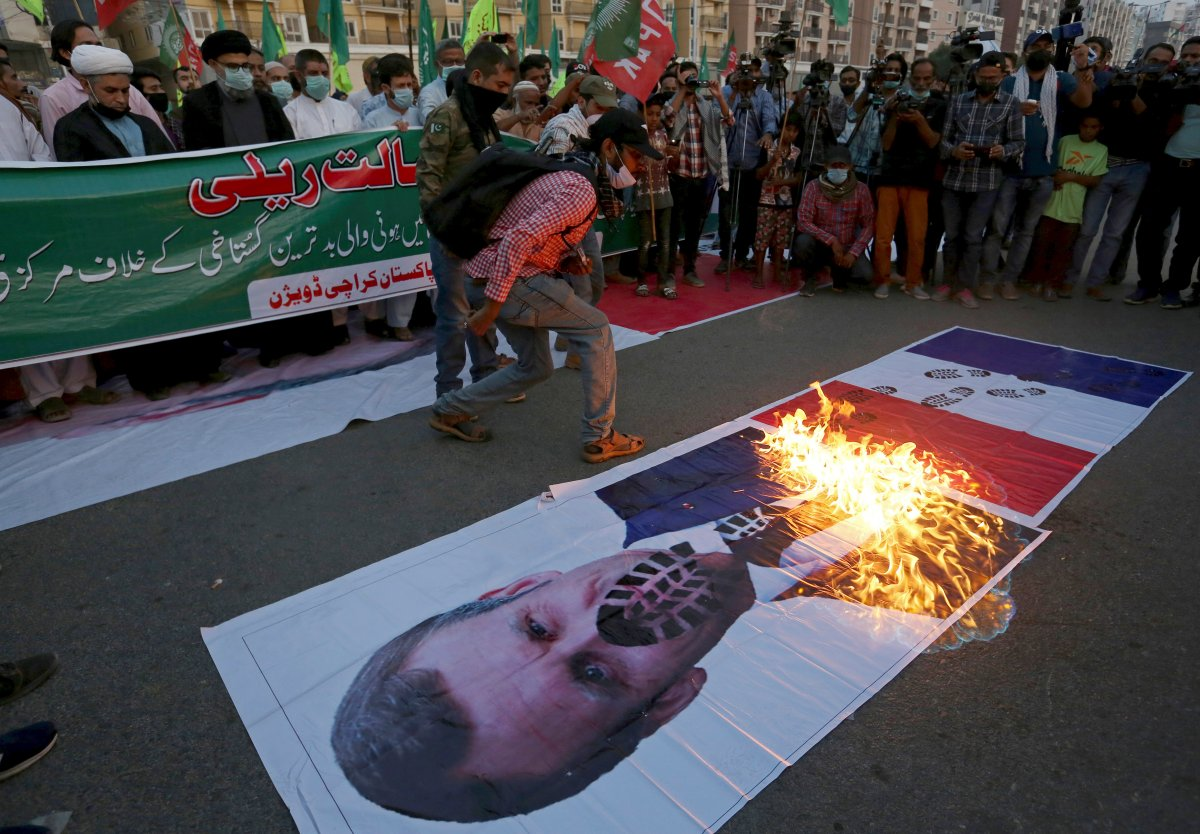 Pakistani Shiite Muslims burn a representation of a French flag and a defaced image of French President Emmanuel Macron during a rally against the French president and the republishing of caricatures of the Prophet Muhammad they deem blasphemous, near the French consulate in Karachi, Pakistan, Nov. 1, 2020.