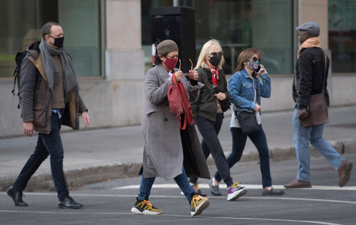 People wear face masks as they walk along a street in Montreal, Saturday, November 7, 2020, as the COVID-19 pandemic continues in Canada and around the world.