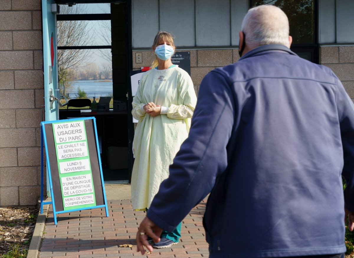 A nurse welcomes a man at a COVID-19 testing clinic in Montreal, on Monday, November 9, 2020.