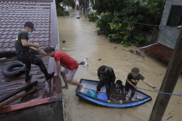 Police rescue residents as floods continue to rise in Marikina, Philippines, due to Typhoon Vamco Thursday, Nov. 12, 2020. A typhoon swelled rivers and flooded low-lying areas as it passed over the storm-battered northeast Philippines, where rescuers were deployed early Thursday to help people flee the rising waters.