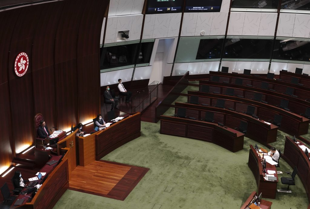 """Empty seats of pro-democracy legislators, top right, are seen at Legislative Chamber in Hong Kong, Thursday day, Nov. 12, 2020. Hong Kong's pro-democracy lawmakers announced Wednesday they would resign en masse after four of them were ousted from the semiautonomous Chinese territory's Legislature in a move one legislator said could sound the """"death knell"""" for democracy there."""