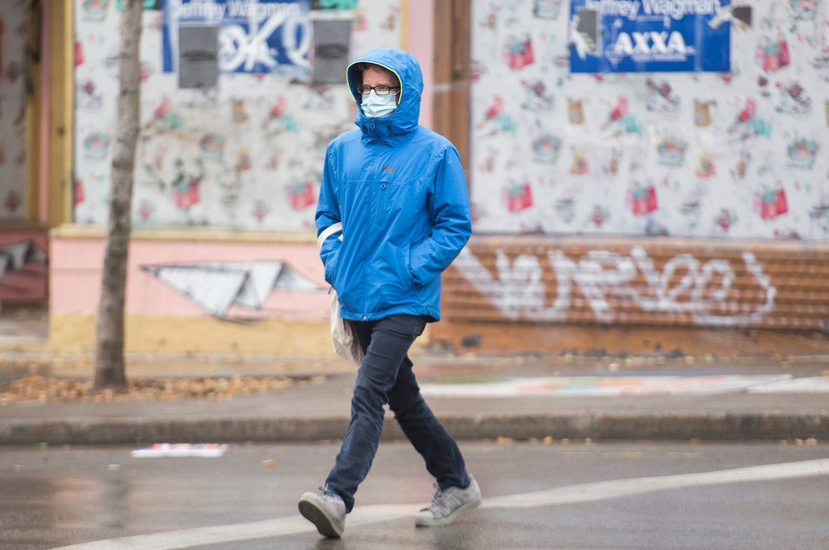 A man wears a face mask as he crosses a street in Montreal, Sunday, November 15, 2020, as the COVID-19 pandemic continues in Canada and around the world.THE CANADIAN PRESS/Graham Hughes.