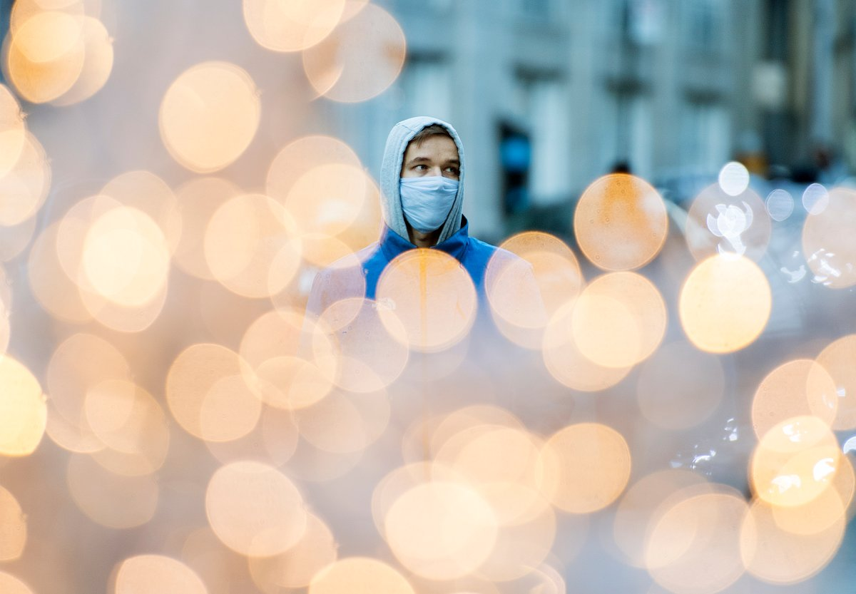 A man wears a face mask as he walks by festive lights in Montreal, Saturday, Nov. 21, 2020, as the COVID-19 pandemic continues in Canada and around the world.