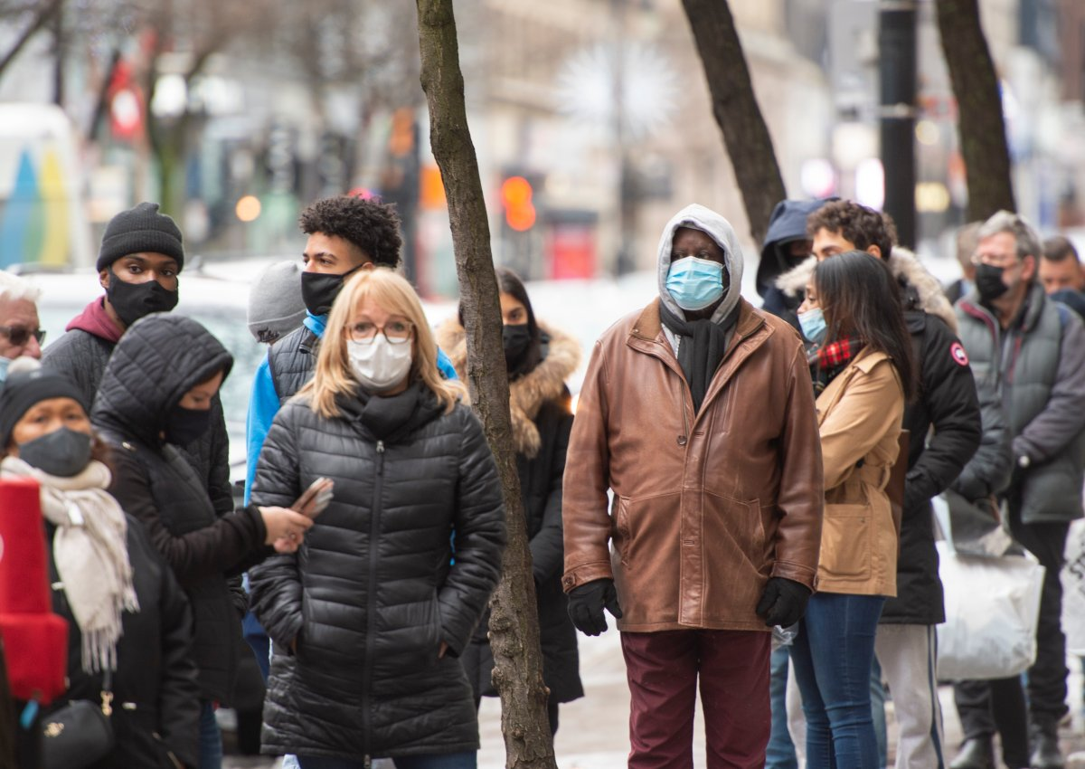 People line up at a store Monday on, Nov. 23, 2020, as the COVID-19 pandemic continues to impact businesses in Montreal.