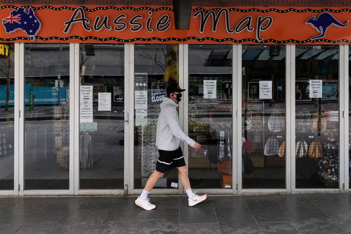 A man walks past a shop closed down store selling Australian paraphernalia items aimed at International tourists during lockdown in Melbourne, Australia, Wednesday, Aug. 5, 2020.