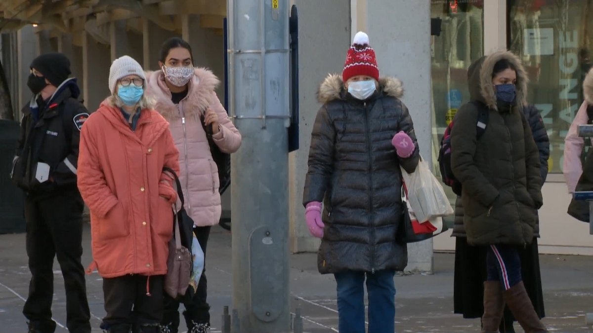 People wearing face masks are seen in downtown Calgary.