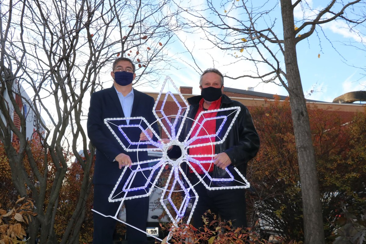 Peterborough-Kawartha MPP Dave Smith and Terry Guiel of Downtown Business Improvement Area of Peterborough showcase new downtown ornaments.