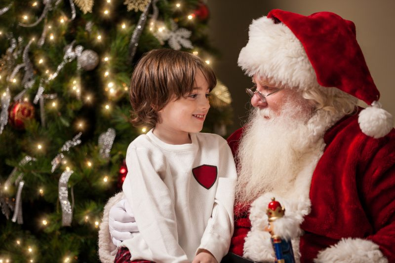 A young boy sits on Santa Claus' lap by a decorated Christmas tree.