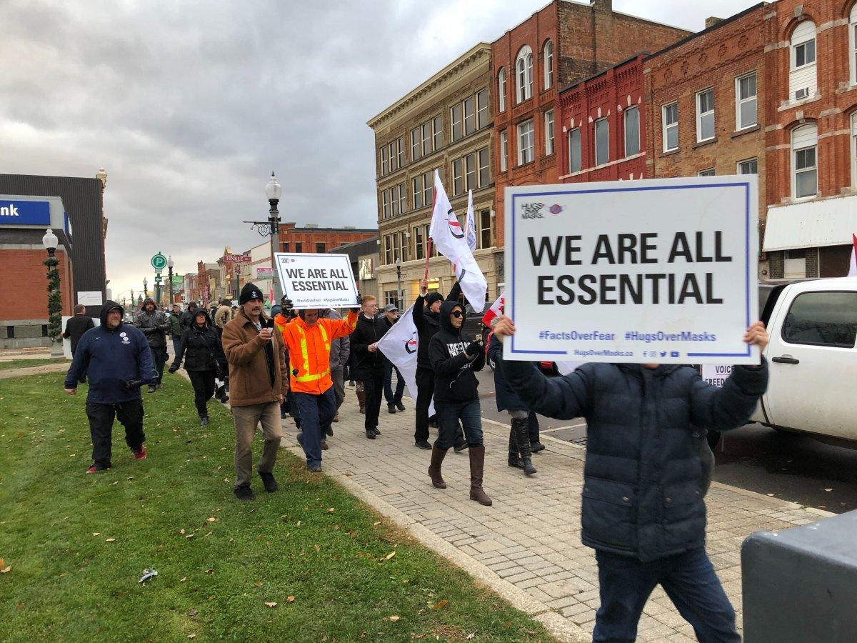 Demonstrators begin a march down Dundas Street following Sunday's anti-lockdown rally in Woodstock.
