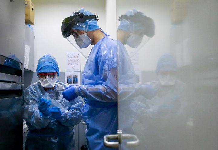 (FILE PHOTO) A nurse dresses in protective clothing to be able to care for a COVID-19 patient.