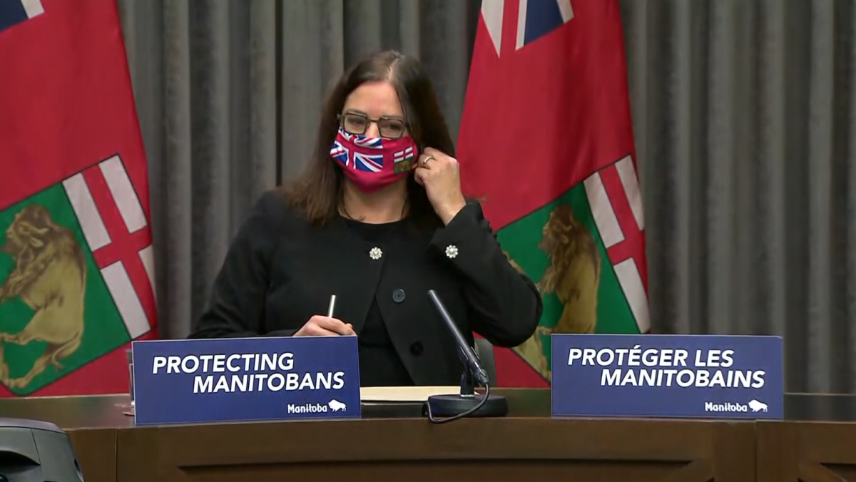 Manitoba families minister Heather Stefanson removing her mask before a media briefing on Friday morning.