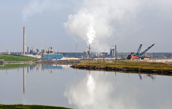 The Syncrude oil sands facility is reflected in a tailings pond near Fort McMurray, Alta., Tuesday, July 10, 2012.