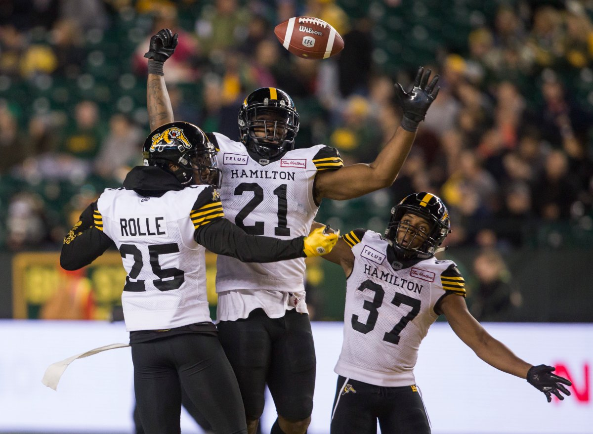 Hamilton Tiger-Cats defensive back Jumal Rolle (25), linebacker Simoni Lawrence (21) and defensive back Frankie Williams (37) celebrate an interception on the Edmonton Eskimos during second half CFL action in Edmonton, Alta., on Friday September 20, 2019. The Tiger-Cats won 30-27.