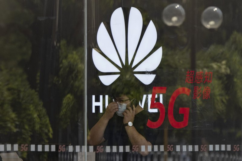 In this Wednesday, July 15, 2020 file photo, a worker wearing a mask to curb the spread of the coronavirus speaks on the phone near the Huawei logo in a store in Beijing.