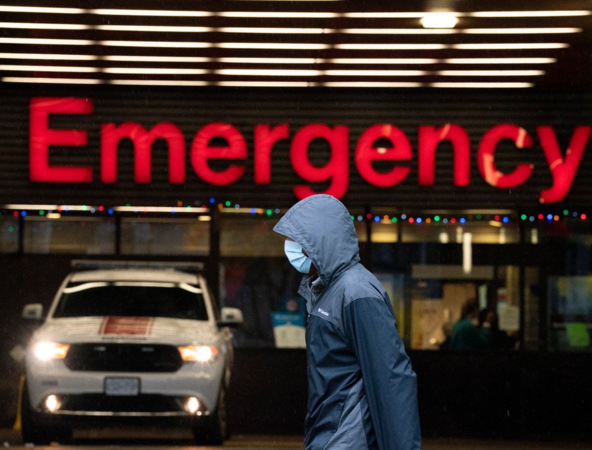 A person wears a protective face mask to help prevent the spread of COVID-19 as they walk past the emergency department of the Vancouver General Hospital in Vancouver Wednesday, November 18, 2020.