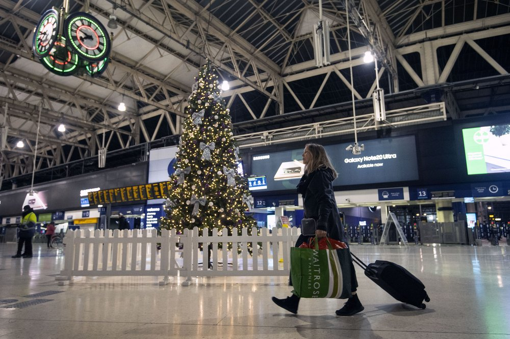 A woman pulls a suitcase past the Christmas tree on the concourse of Waterloo Station in central London, Sunday, Dec. 20, 2020. Millions of people in England have learned they must cancel their Christmas get-togethers and holiday shopping trips. British Prime Minister Boris Johnson said Saturday that holiday gatherings can't go ahead and non-essential shops must close in London and much of southern England.