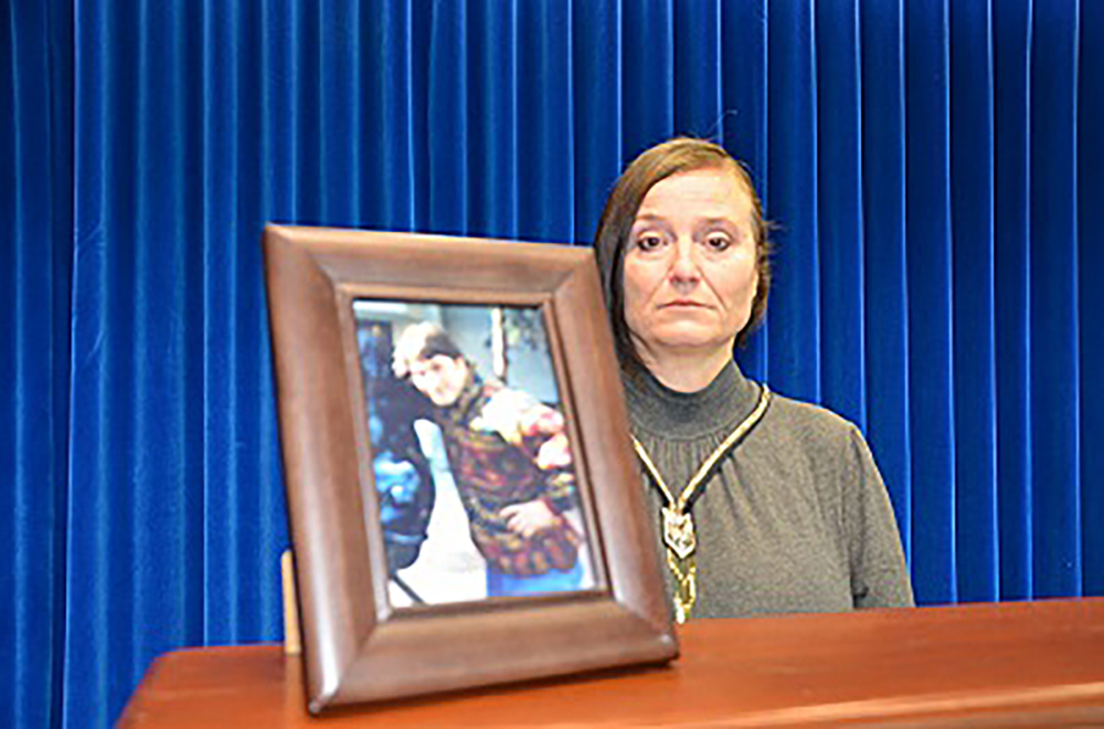 A photo from the RCMP showing Paulina with a photo of her brother, Joseph Pek.