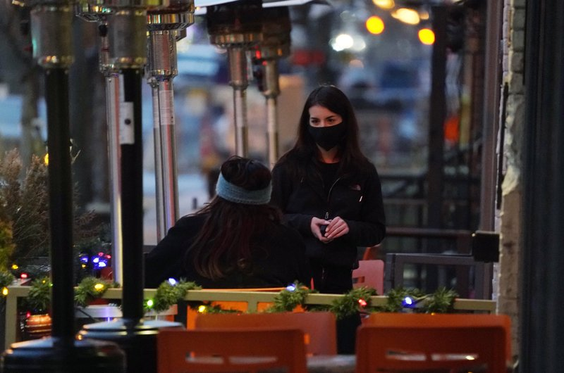 A waitperson wears a face mask while tending to a patron sitting in the outdoor patio of a sushi restaurant, late Monday, Dec. 28, 2020, in downtown Denver.