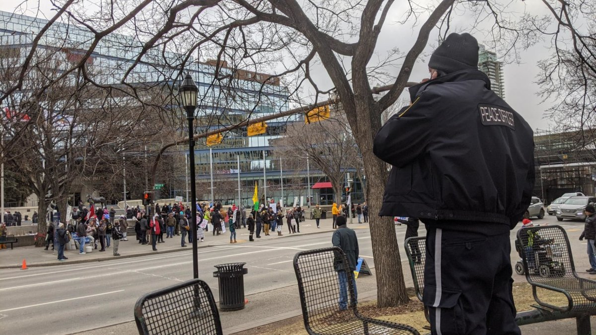 A peace officer watches as another rally is held in Calgary to protest government COVID-19 restrictions, Saturday, Dec. 12, 2020.