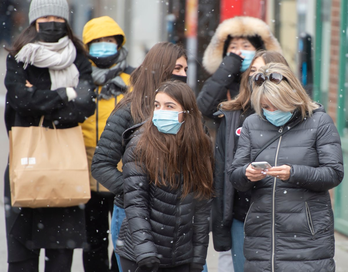 Pedestrians protect themselves from the cold and COVID-19 as they wait for a light to change, Tuesday, November 3, 2020  in Montreal.