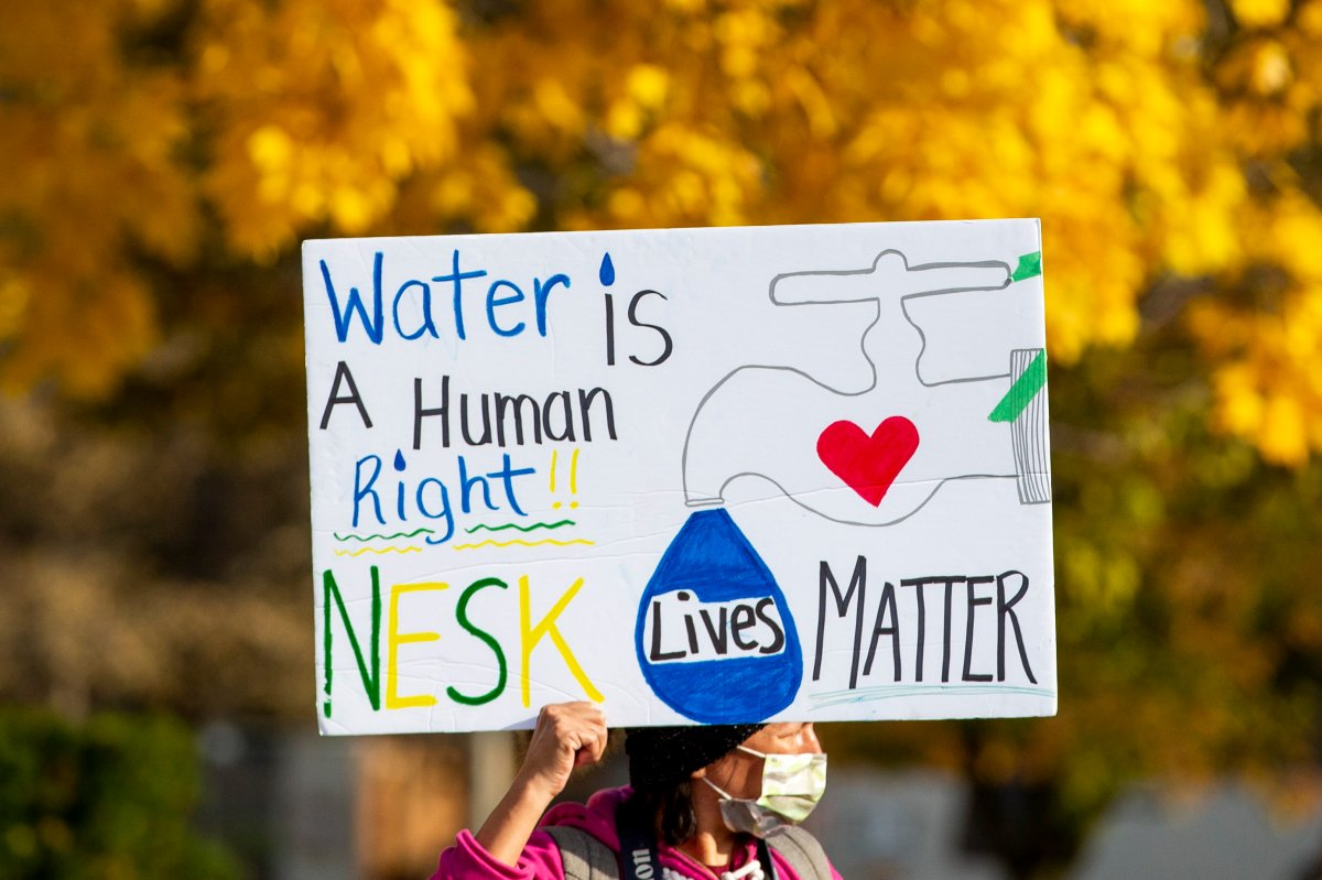 A sign is held up as people stand in solidarity with the people of Neskantaga First Nation, where residents were evacuated over tainted water last month, outside Queen's Park in Toronto on Friday, November 6, 2020. THE CANADIAN PRESS/Carlos Osorio
