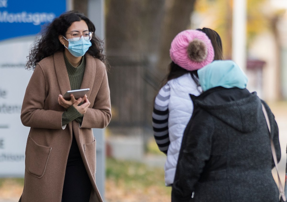 A health-care worker talks to people as they wait to be tested for COVID-19 at a testing clinic in Montreal, Sunday, October 25, 2020, as the COVID-19 pandemic continues in Canada and around the world.