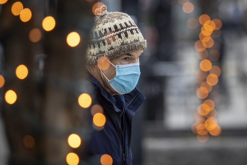 A person wears a mask, while framed through Christmas lights in Kingston, Ontario on Monday, November 23, 2020, as the COVID-19 pandemic continues across Canada and around the world. THE CANADIAN PRESS IMAGES/Lars Hagberg.