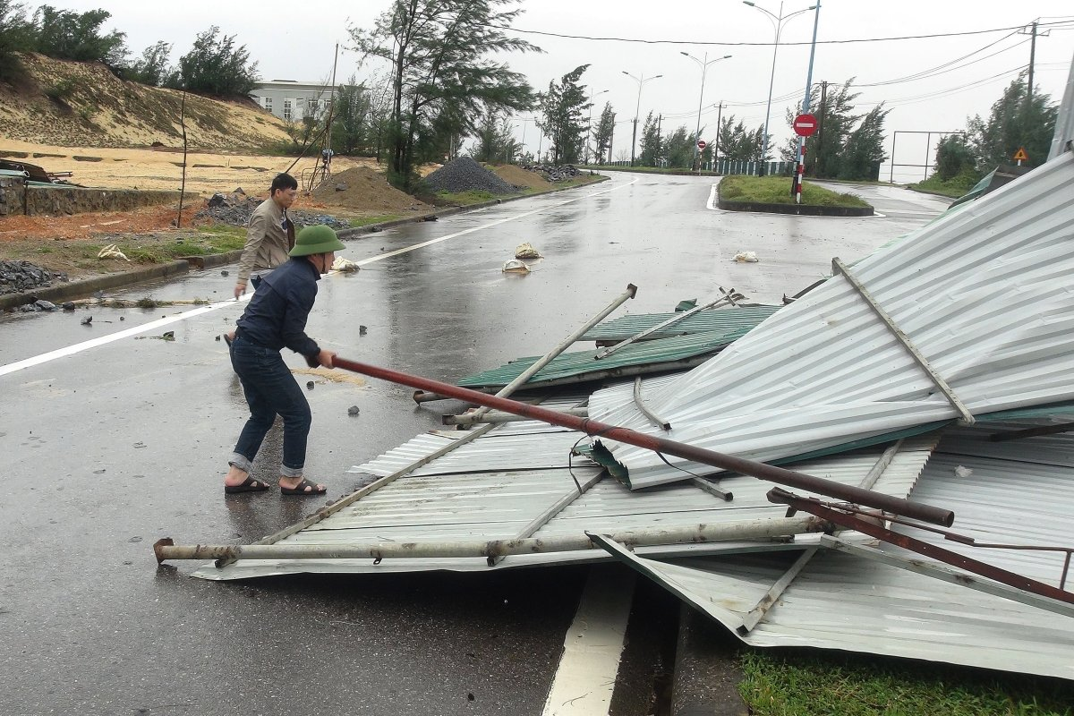 People clean up the street after typhoon Vamco passed, in Quang Binh, Vietnam, 15 November 2020. Typhoon Vamco made landfall in the country's central coast on 15 November 2020.