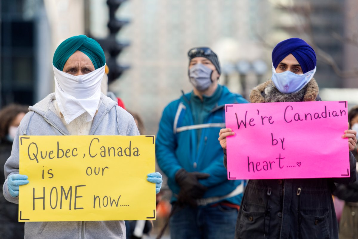 People take part in a demonstration outside Quebec Premier Francois Legault's office in Montreal, Saturday, Nov. 21, 2020, where they called on the government to give permanent residency status to all migrant workers and asylum seekers. The COVID-19 pandemic continues in Canada and around the world.