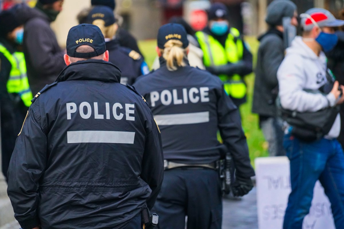 Montreal police officers watching to see if people are respecting social-distancing at a protest in Montreal, Saturday, Nov. 28, 2020.