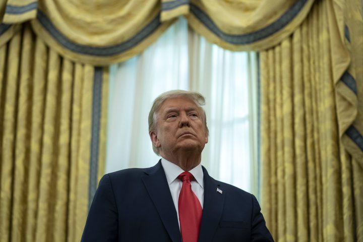FILE: U.S. President Donald Trump listens during a ceremony to present the Presidential Medal of Freedom to former football coach Lou Holtz, in the Oval Office of the White House, Thursday, Dec. 3, 2020, in Washington.