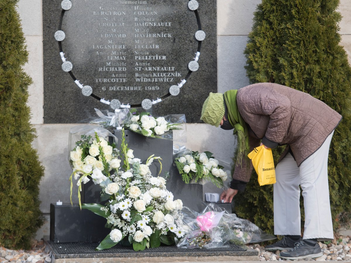 Marie Bolduc places candles on the commemorative plaque on the wall of Polytechnique in Montreal, Sunday, Dec. 6, 2020, on the 31st anniversary of the murder of 14 women in an anti-feminist attack at École Polytechnique on December 6, 1989. The COVID-19 pandemic continues in Canada and around the world.