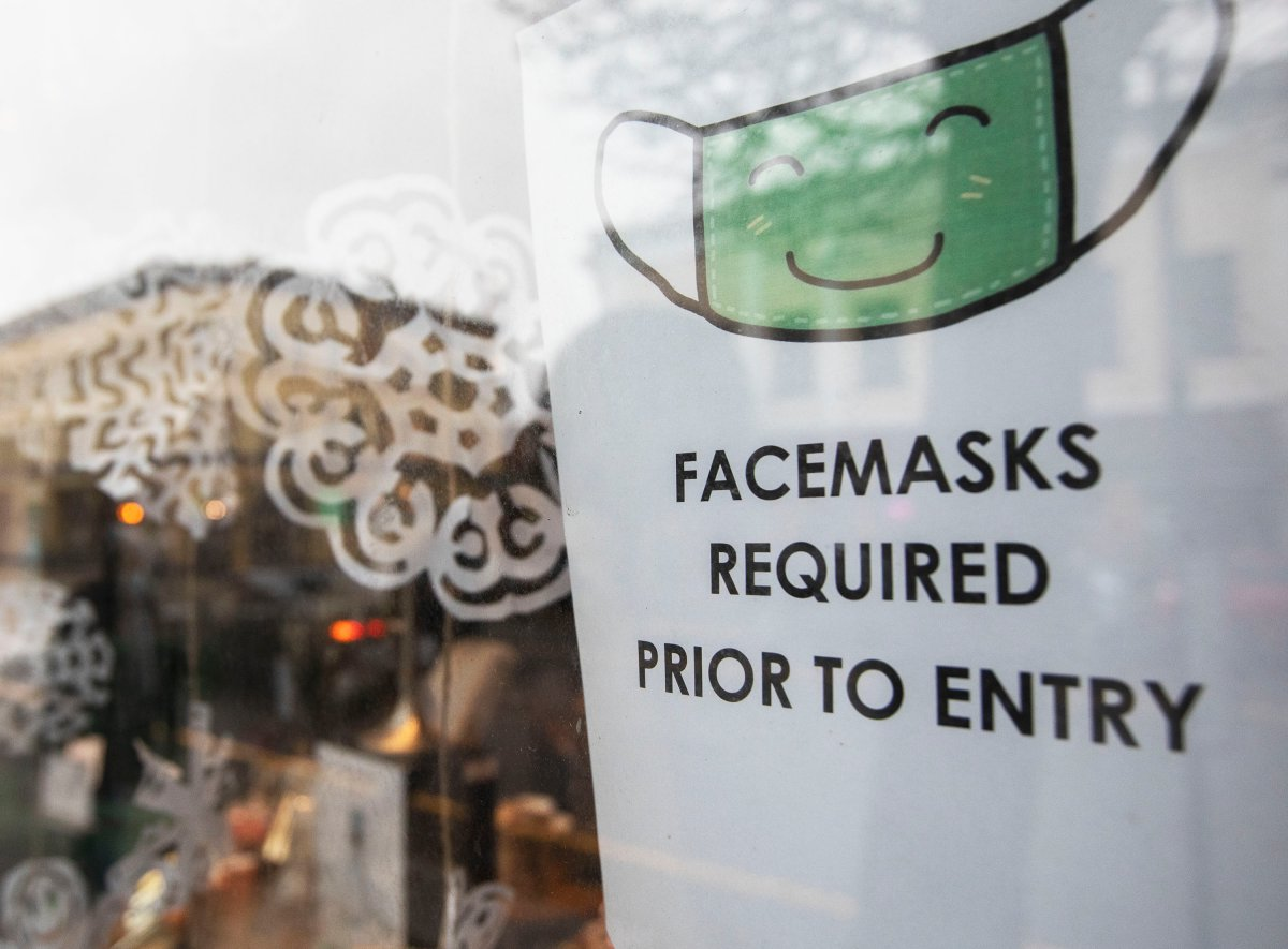 A sign letting customers know they must wear a mask inside is seen in a business' window in downtown Victoria, B.C. on Monday, Dec. 7, 2020. Masks are required in all indoor public spaces in B.C. THE CANADIAN PRESS/Marissa Tiel.