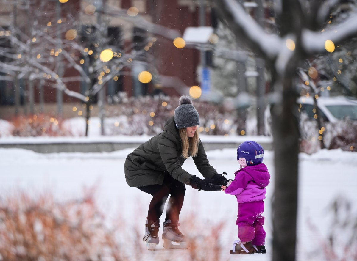 A mom teachers her daughter to skate at Landsdowne Park in Ottawa on Wednesday, Dec. 9, 2020.