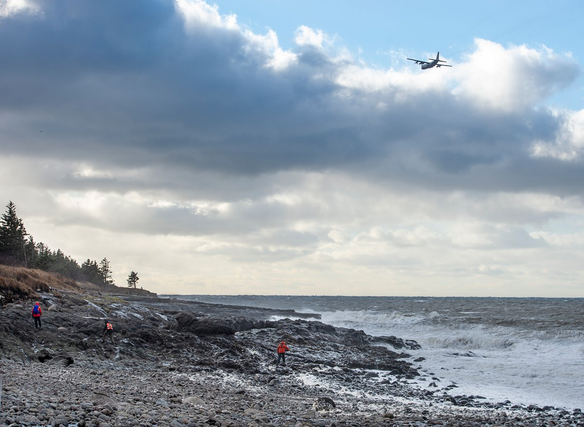 An RCAF Hercules aircraft scours the waters as members of a ground search and rescue team walk along the shore of the Bay of Fundy in Hillsburn, N.S., in an area where empty life-rafts from a scallop fishing vessel where reported on Tuesday, Dec. 15, 2020.