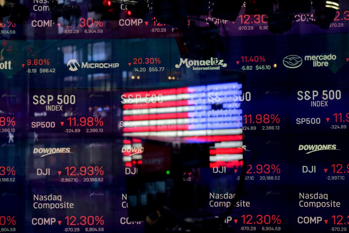A United States flag is reflected in the window of the Nasdaq studio, which displays indices and stocks down, in Times Square, New York, Monday, March 16, 2020.