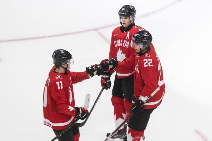Canada's Cole Perfetti (11), Dylan Cozens (22) and Connor McMichael (17) celebrate a goal against Switzerland during second period IIHF World Junior Hockey Championship action in Edmonton on Tuesday, December 29, 2020.