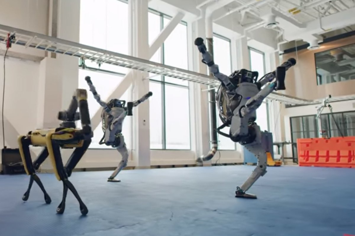 Two Atlas robots and a Spot dance at a Boston Dynamics facility in this image from video released Dec. 29, 2020.