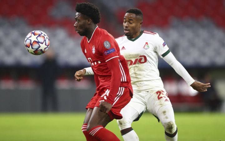 Bayern's Alphonso Davies, left, controls the ball in front of Lokomotiv's Francois Kamano, right, during the Champions League Group A soccer match between Bayern Munich and Lokomotiv Moscow at the Allianz Arena in Munich, Germany, Wednesday, Dec. 9, 2020.
