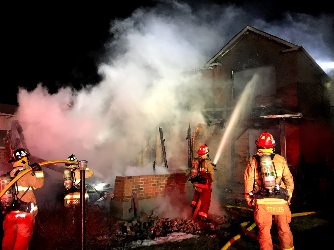 Firefighters work to extinguish a fire at a house on Hansen Avenue.