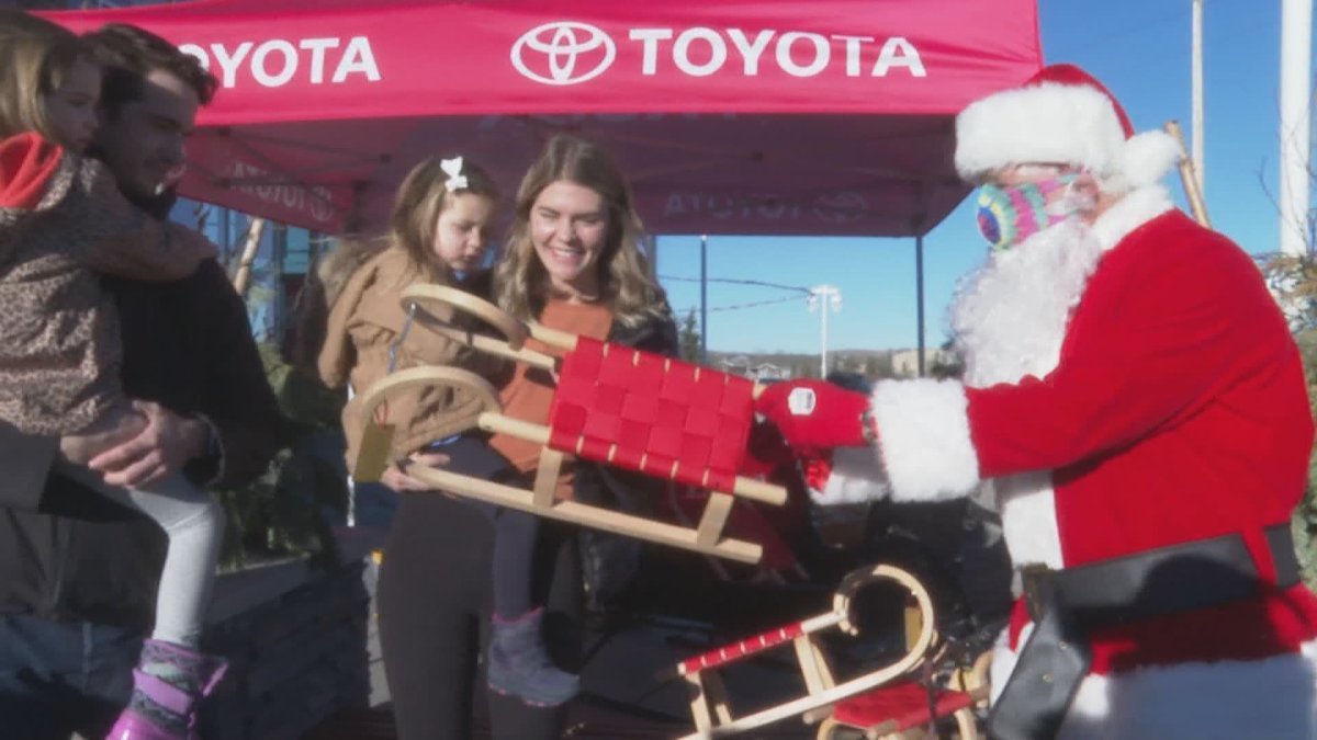 Hundreds of sleds and toys were donated to Calgary kids, including to Lukah Mitchell, seen with her mother Tanis on Sunday, Dec. 20, 2020.