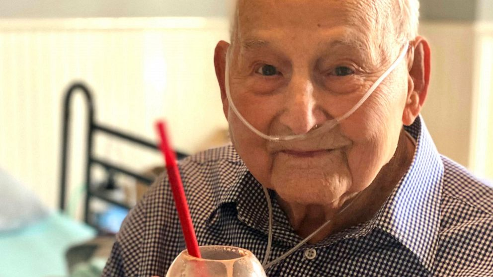 In this photo provided by Holly Wooten McDonald, World War II veteran and COVID-19 survivor Major Wooten holds a celebratory milkshake on his 104th birthday on Thursday, Dec. 3, 2020, in Madison, Alabama.