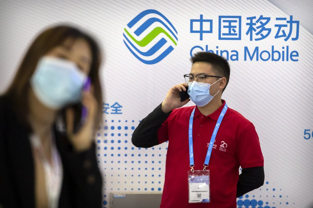 People wearing face masks to protect against the spread of the coronavirus talk on their cellphones near a booth for Chinese telecommunications firm China Mobile at the PT Expo in Beijing on Oct. 14, 2020. China said Saturday, Jan. 2, 2021, that it would take necessary countermeasures in response to the New York Stock Exchange's announcement that it would delist three major Chinese telecoms, in the latest flare-up of tensions between Beijing and Washington.