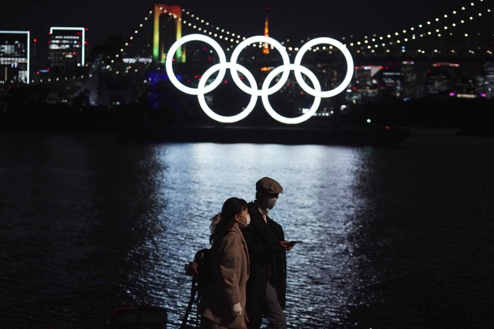 In this Dec. 1, 2020, file photo, a man and a woman walk past near the Olympic rings floating in the water in the Odaiba section in Tokyo.