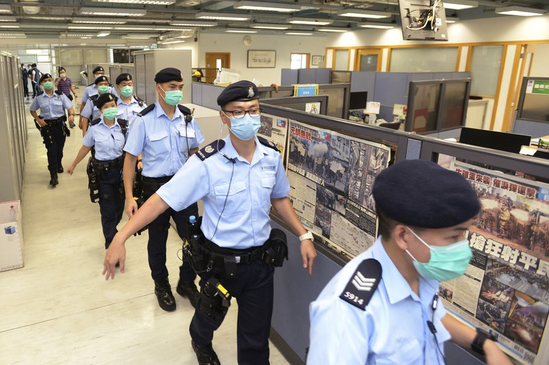 In this Monday, Aug. 10, 2020, photo, police officers take enter the Apple Daily newspaper headquarters as founder Jimmy Lai is arrested by police officers at his home in Hong Kong. Seven human rights experts affiliated with the U.N. raised concerns over Hong Kong's national security law in a letter addressed to Chinese authorities, saying that the law infringed on certain fundamental rights.