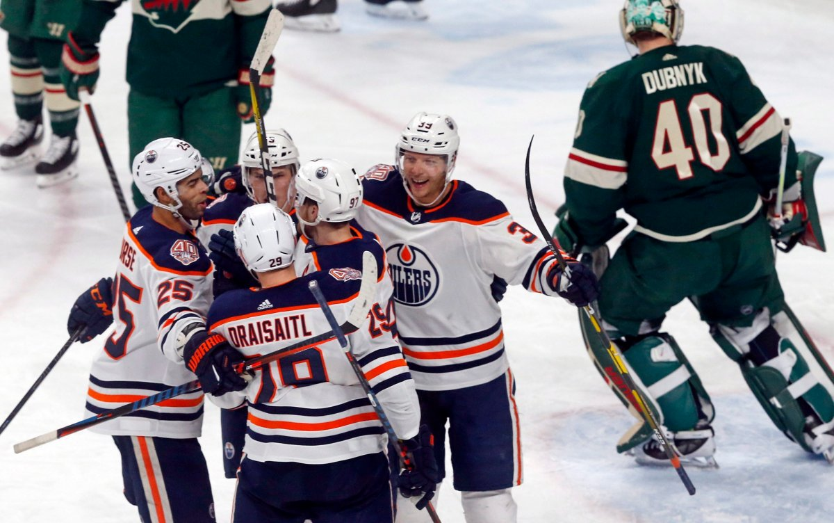 Edmonton Oilers' Leon Draisaitl, back to camera, of Germany, is congratulated by teammates after his power-play goal against Minnesota Wild goalie Devan Dubnyk, right, during the third period of an NHL hockey game Thursday, Feb. 7, 2019 in St. Paul, Minn. At left is Oilers' Darnell Nurse, who scored a first-period goal. The Oilers won 4-1;(AP Photo/Jim Mone).