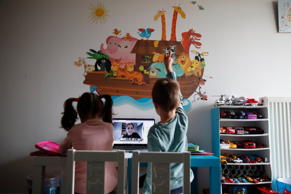 A kindergarten teacher reads a fairy story as Panos raising his hand with his twin sister Marina watch the online lesson in Athens, Greece. Thursday, Nov. 19, 2020. (AP Photo/Thanassis Stavrakis).